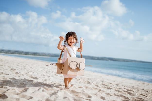 Criança correndo na praia brincando com um aviãozinho de papelão