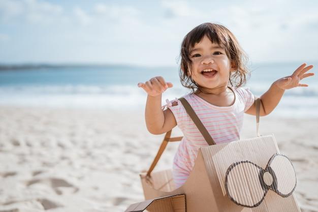 Criança correndo na praia brincando com um aviãozinho feito de papelão
