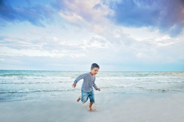 Criança correndo na praia. férias de verão. garoto feliz jogando na praia na hora do sol
