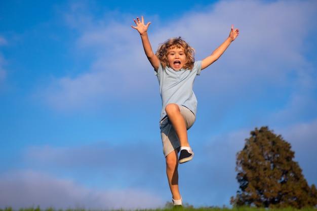 Criança correndo no campo de grama. menino bonito correr no parque de verão. criança correndo no prado.