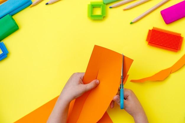 Criança corta papel laranja com tesoura em uma mesa para alguns trabalhos manuais