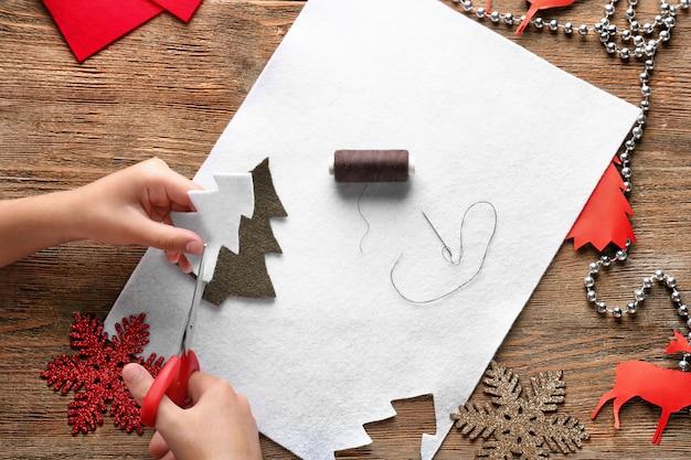 Criança cortando árvore de natal de feltro na mesa