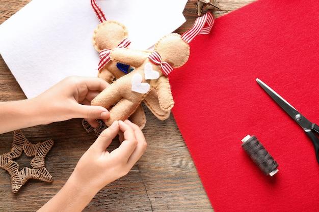 Criança costurando um brinquedo de feltro na mesa de natal