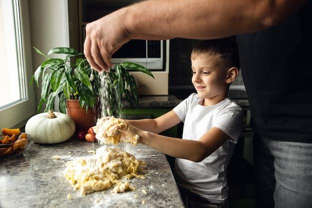 Criança cozinhando com o pai na cozinha. menino ajuda a fazer massa para biscoitos. rapaz maroto. atividade interna.