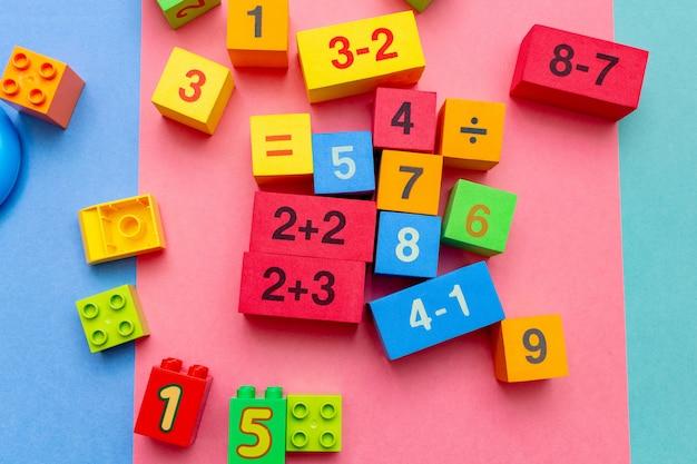 Criança criança educação colorida brinca cubos com números. postura plana.