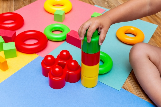 Criança criança jogando brinquedos coloridos educação no fundo brilhante. conceito de bebês de crianças infância.
