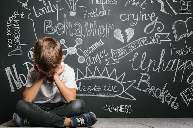 Criança cuja depressão está em um quadro negro com as mãos fechadas