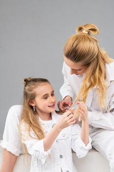 Criança curiosa de cabelos compridos observando os cabelos mais claros de sua irmã mais velha enquanto se apoia em suas pernas no estúdio