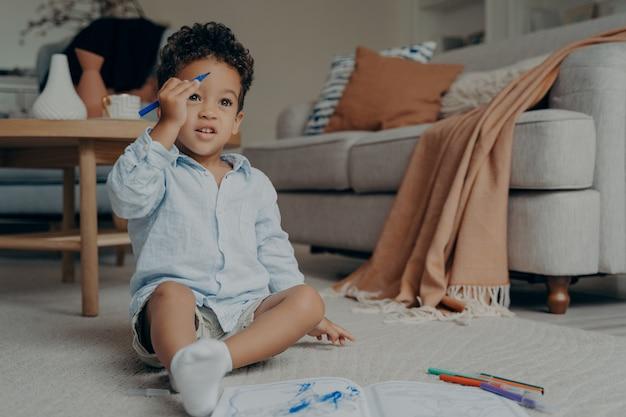 Criança curiosa de raça mista com roupas casuais e meias brancas sentada no chão enquanto desenha no álbum