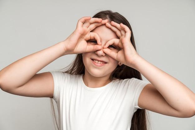Criança curiosa explorando o mundo. retrato de uma menina curiosa e intrometida olhando através de dedos em forma de binóculo e expressando espanto