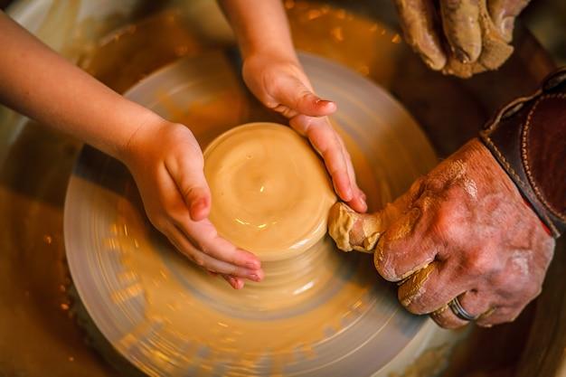 Criança da arte de fazer um pote ou um vaso de barro