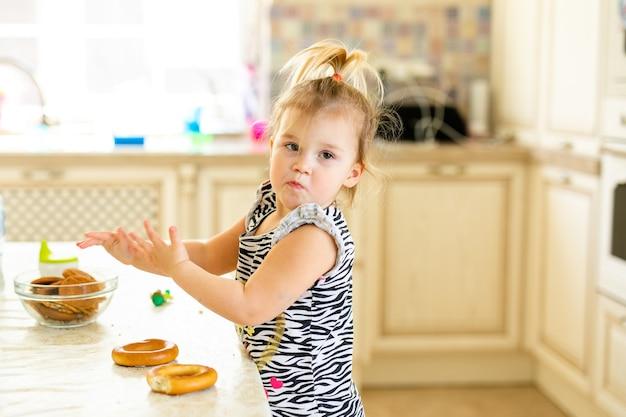 Criança da criança almoçando na cozinha quente e ensolarada. menina loira com rabo de cavalo engraçado brincando com dois saborosos bagels.
