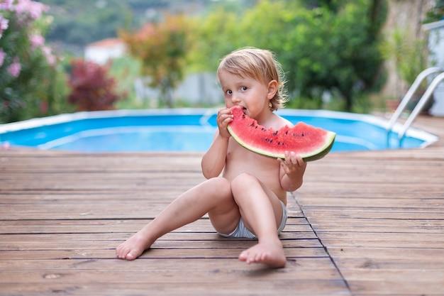 Criança da criança comendo melancia perto da piscina durante as férias de verão. as crianças comem frutas ao ar livre. lanche saudável para crianças. menino brincando no jardim segurando uma fatia de melancia.