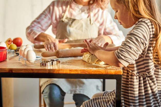 Criança da família com a mãe abrindo a massa usando o rolo em uma sala iluminada