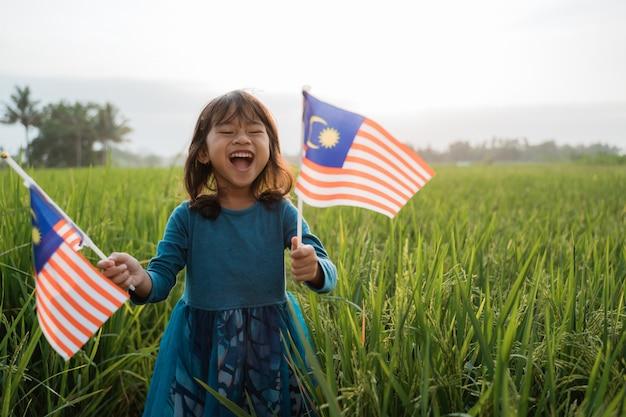 Criança da malásia com bandeira nacional
