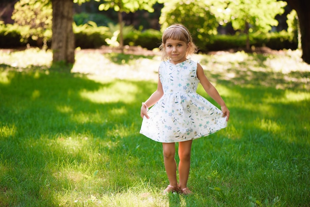 Criança da menina de llittle ao ar livre no dia de verão.