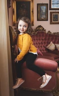 Criança da menina em uma sala de visitas com decoração barroca.