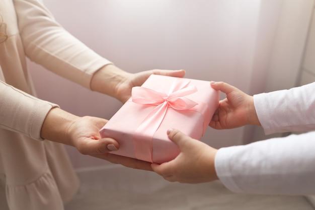 Criança dando uma caixa de presente para a mãe. férias, presente, conceito de infância. perto das mãos da criança e da mãe com caixa de presente em fundo branco. dia das mães, dia das mulheres (8 de março), páscoa.
