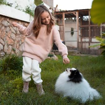 Criança dando uma guloseima para o cachorro