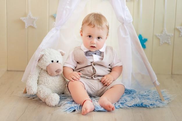 Criança de 1 ano, um menino de terno senta-se com um urso em uma tenda