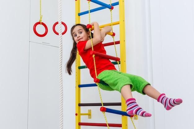 Criança de 7 anos de idade, jogando no equipamento desportivo