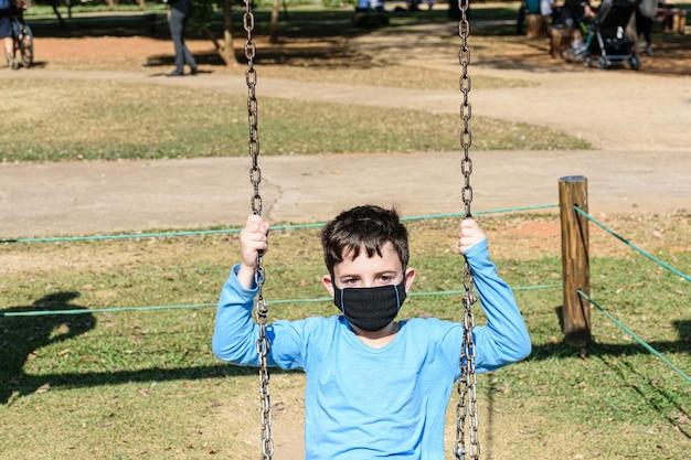 Criança de 8 anos, com máscara, brincando de balanço em dia de sol (vista frontal).