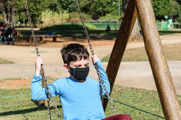 Criança de 8 anos, com máscara, brincando em um balanço em um dia ensolarado.