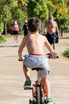 Criança de 8 anos, sem camisa, andando de bicicleta de costas um para o outro em um dia de sol no parque público.
