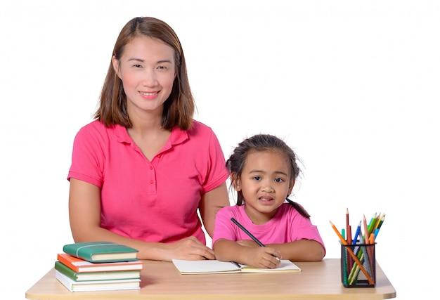 Criança de ajuda nova do professor com lição da escrita isolada no fundo branco