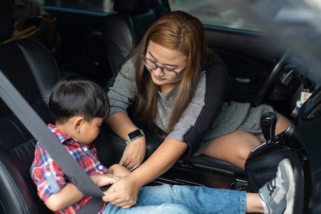 Criança de aperto de mulher asiática com cinto de segurança no carro.