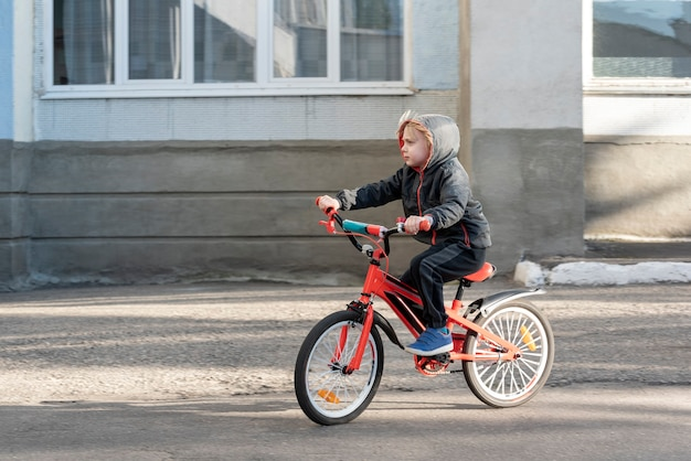Criança de bicicleta em estrada pavimentada. o menino aprende a montar.