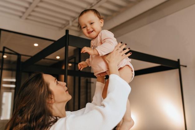 Criança de blusa bege fica feliz que sua mãe a joga para cima, brincando com ela em um apartamento aconchegante.