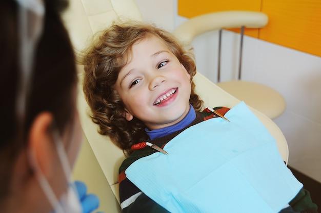 Criança de cabelo encaracolado se entrega e faz careta em uma cadeira odontológica