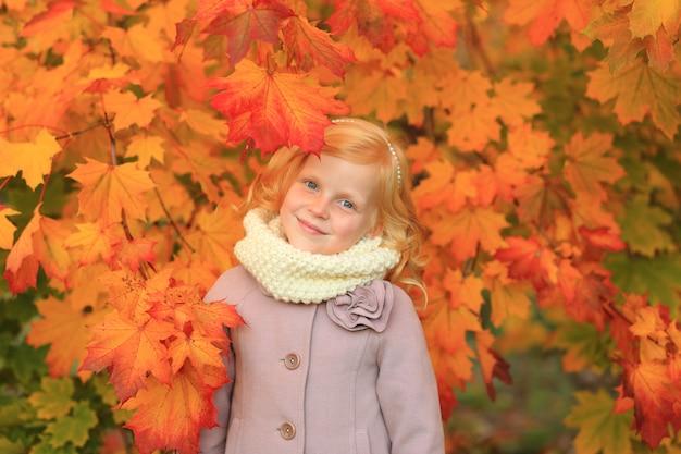 Criança de cabelo vermelho no outono