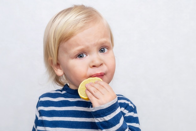 Criança de cabelos loiro come limão azedo em branco