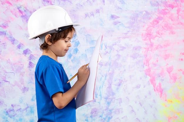 Criança de camiseta azul e capacete branco segurando o plano de papel perto da parede colorida