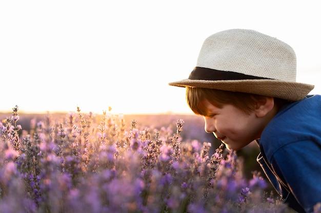 Criança de close-up, cheirando flores