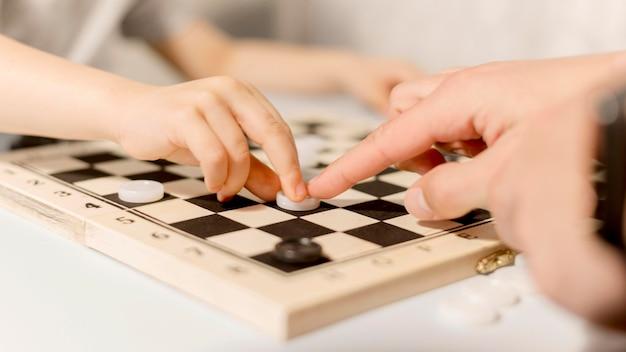 Criança de close-up jogando xadrez