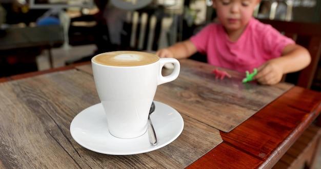 Criança de companhia de cappuccino com sabor de copo