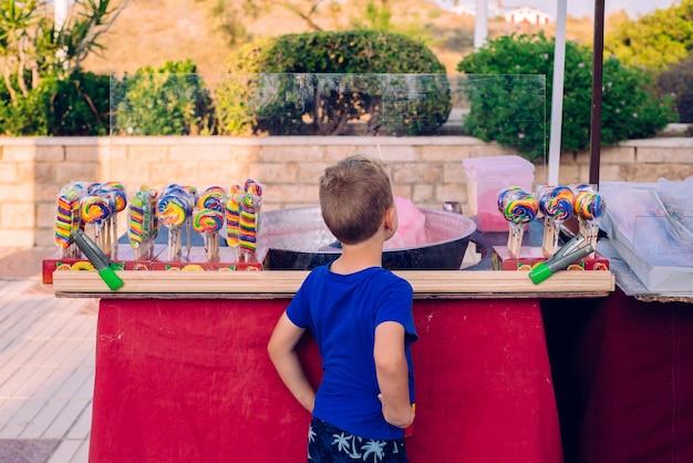 Criança de costas olhando para uma barra de chocolate em uma feira