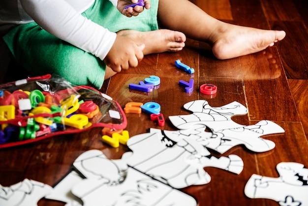 Criança de descendência africana desfrutando de quebra-cabeças