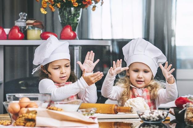 Criança de duas meninas felizes cozinhando com farinha e massa na mesa da cozinha é linda e linda