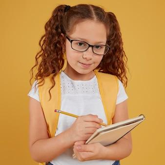 Criança de frente escrevendo e olhando para a câmera