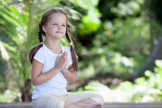 Criança de ioga fazendo exercício na plataforma de madeira entre plantas verdes ao ar livre.