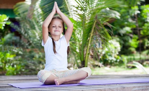 Criança de ioga fazendo exercícios de fitness na plataforma da praia ao ar livre.
