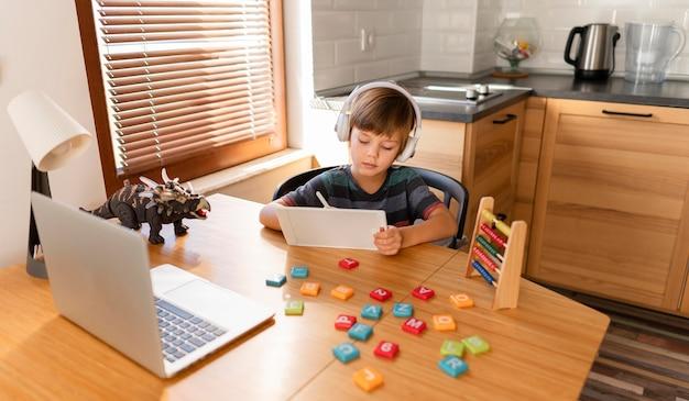 Criança de longo alcance participando de cursos escolares virtuais