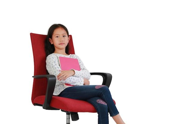 Criança de menina asiática abraçando um livro sentado na cadeira de tecido vermelho, isolada no fundo branco. imagem em estúdio com caminho de recorte