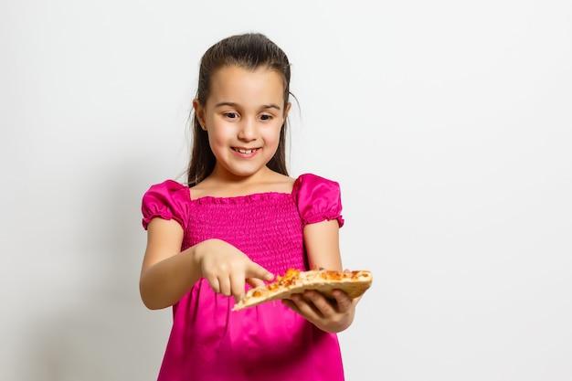 Criança de menina asiática asiática pequena comendo pizza saborosa. em pé, isolado sobre um fundo branco.
