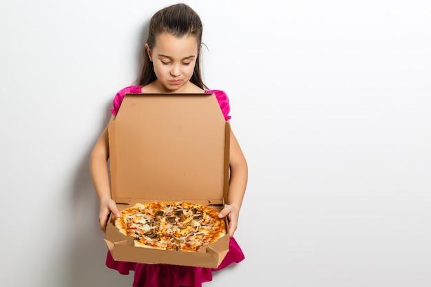 Criança de menina asiática indiana bonitinha comendo pizza saborosa na caixa. em pé, isolado sobre um fundo branco.