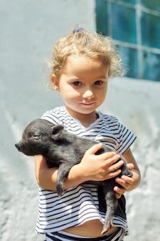 Criança de menina criança segurando nas mãos de leitão preto bebê recém-nascido. fazenda, agricultura, país, animais de estimação, conceito de crianças